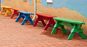 Primary Colored Benches in Row on Bricks Royalty Free Stock Photos