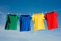 Primary Colored T-Shirts. A set of primary colored T-shirts hanging on a clothesline on a beautiful, sunny day, add text or graphic to shirts or copy space Stock Images