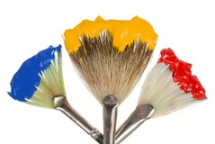 Primary Colors on fan brushes. Three fan-shaped paintbrushes with vibrant primary colors, isolated on white royalty free stock photo