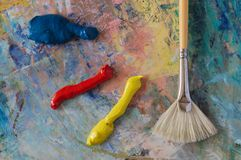 Primary colours on a palette. With a fan brush stock photography