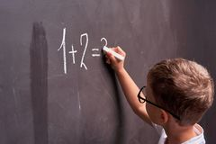 Primary education. Rear view of a schoolboy solves a mathematical example on a blackboard in a math class royalty free stock photos