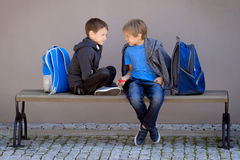 Primary education, school, friendship concept - two boys with backpacks sitting, talking and playing with spinner. After school Royalty Free Stock Photos