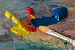 Primary oil colours and a brush. On a wooden palette stock photos