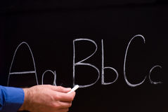 Primary School. Closeup view of a teacher holding some chalk and writing basic letters on a blackboard Royalty Free Stock Image