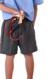Primary school boy. Kid in primary school with naughty look and slingshot behind back Royalty Free Stock Images