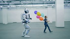 Primary school education concept. Girl and robot walking in aroom, side view. A kid walks in a room with droid stock footage