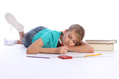 Primary school girl doing math homework on floor Royalty Free Stock Photos
