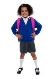Primary school girl posing confidently. With hands on her waist, carrying pink school bag Royalty Free Stock Photography