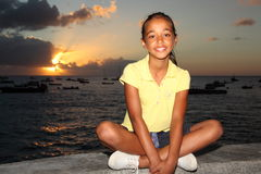 Primary school girl sitting by the sea at sunset Stock Photos