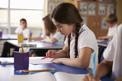 Primary school girl working at her desk in class Stock Photos