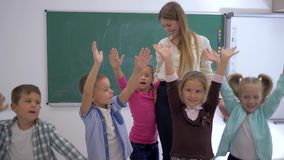 Primary school, group of children fun jumping and waving hands near to the teacher on background of the board