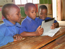 Primary  school kids in class with a tablet phone. Norton,Zimbabwe,January  19 2016.Three primary  school children  using  a  tablet (cellphone) in  a Royalty Free Stock Photo