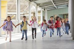 Primary school kids run holding hands in corridor, close up stock images
