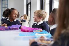 Primary school kids sitting at table eating their packed lunches and talking, close up royalty free stock photo