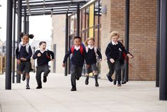 Primary school kids, wearing school uniforms and backpacks, running on a walkway outside their school building, front view stock image