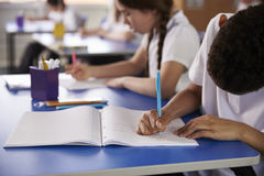 Primary school kids writing at heir desks, close up Stock Image