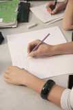 Primary school kids writing with pencils at their desks, close up Royalty Free Stock Image