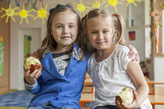 Primary school mates. Primary school pupils eating apples in the classroom Royalty Free Stock Photography