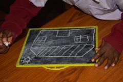 In a primary school, a picture is being drawn on a slate with chalk stock photos