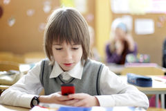 Primary school pupil writting message. Primary school pupil writting text message by cell phone Royalty Free Stock Photos