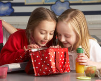 Primary School Pupils Enjoying Packed Lunch In Cla. Ssroom Smiling royalty free stock photography