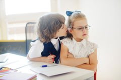 Primary school pupils sit at one desk. Royalty Free Stock Photo