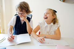 Primary school pupils are sitting at the same desk. Stock Photos