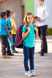 Primary school student. Happy primary school student carrying backpack with classmates and teacher on background royalty free stock photography