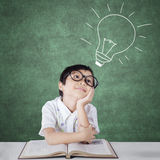 Primary school student imagining a light bulb Royalty Free Stock Photos