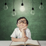 Primary school student sits under light bulb. Picture of a cute female primary school student sitting in the classroom while looking at light bulb with a book on Royalty Free Stock Image