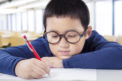 Primary school student writes on the paper. Portrait of a cute boy studying in the classroom while wearing glasses and write on the paper Stock Images