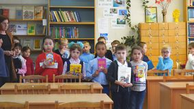 Primary school students stand in front of the camera with books in their hands. Chapaevsk, Samara region, Russia - May 10, 2019: Elementary school of the city of stock video
