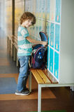The primary school students standing near lockers in hallway. The primary school students standing near lockers in school hallway. He put the backpack on the stock image