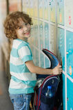 The primary school students standing near lockers in hallway. The primary school students standing near lockers in school hallway. He put the backpack on the Royalty Free Stock Images