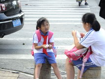 Primary school students waiting for the school bus Stock Image