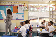 Primary school teacher writing on a flip chart in a lesson Stock Images