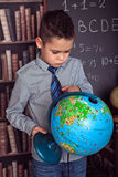 Primary schoolboy studying globe Royalty Free Stock Images