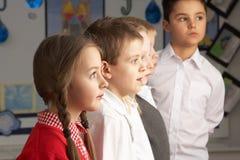 Primary Schoolchildren Standing In Classroom Stock Image