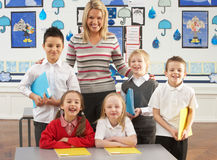 Primary Schoolchildren And Teacher At Desk Stock Photography