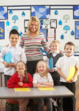 Primary Schoolchildren And Teacher At Desk Stock Photo