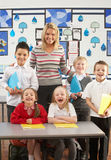 Primary Schoolchildren And Teacher At Desk Stock Image