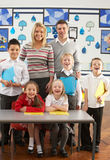 Primary Schoolchildren And Teacher At Desk Royalty Free Stock Images
