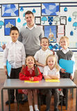 Primary Schoolchildren And Teacher At Desk Stock Images