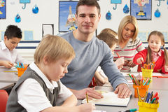 Primary Schoolchildren And Teacher Having A Lesson Royalty Free Stock Photography
