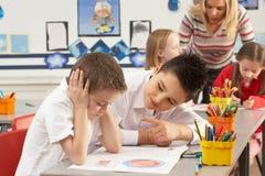 Primary Schoolchildren And Teacher Working stock images