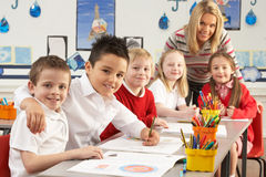 Primary Schoolchildren And Teacher Working. Group Of Primary Schoolchildren And Teacher Working At Desks In Classroom Royalty Free Stock Photos