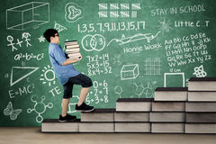 Primary student carrying books on stair. Image of primary student carrying pile of books while walking on books stair with doodle and scribble on chalkboard Royalty Free Stock Photos