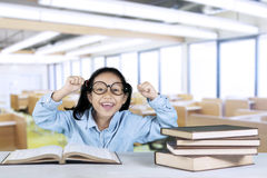 Primary student celebrating her success in classroom. Primary student celebrating her success while sitting in the classroom with books on table royalty free stock images