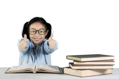 Primary student showing ok gesture with books Stock Image