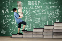 Primary student walking on books stair. Picture of primary student walking on books stair while holding pile of books with doodle on chalkboard Stock Photography